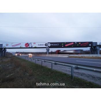Изготовление и монтаж баннеров 50х3м (2шт) на рекламную конструкцию на мосту на Киевской трассе для ..
